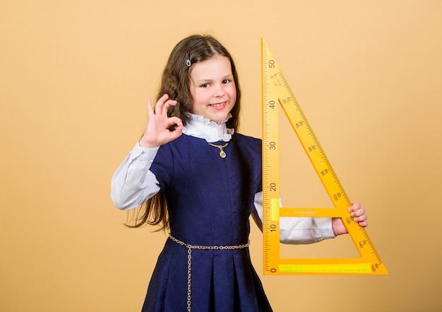 Concetto intelligente e intelligente. allievo ragazza carina con grande righello. geometria di studio dello studente della scuola. dimensionamento e misurazione. righello della tenuta dell'uniforme scolastica per bambini. istruzione e concetto di scuola. amo la matematica.