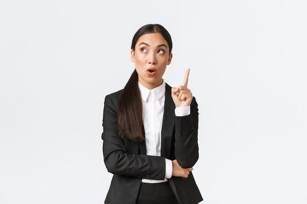 La donna di affari asiatica astuta e creativa ha un'idea eccellente che alza il dito e guarda pensieroso suggerire la soluzione nell'angolo in alto a sinistra fare un piano dicendo il pensiero sul muro bianco