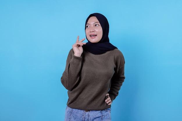 Collaboratrice femminile dall'aspetto serio e creativo intelligente che pensa a una concentrazione profonda che riflette sull'idea che fa una scelta toccando il mento con uno sguardo premuroso sul muro blu
