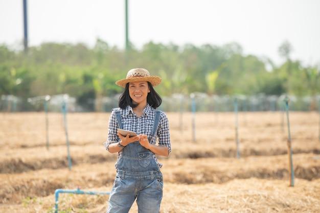 Fattoria intelligente. bella contadina usa la tavoletta per controllare la sua fattoria e il suo business con felice e sorriso. concetto di affari e agricoltura. l'agricoltore o l'agronomo esaminano preparare un appezzamento per la coltivazione di ortaggi.