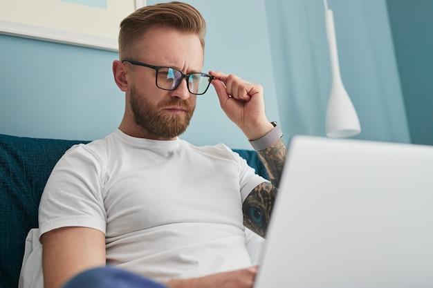 Libero professionista intelligente che utilizza il laptop a casa