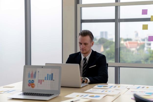 Un bell'uomo d'affari caucasico intelligente si concentra sul lavoro con il laptop sulla scrivania delle riunioni in un ufficio moderno con fiducia. computer tablet con grafici, diagrammi e grafici sullo schermo. analisi finanziaria.