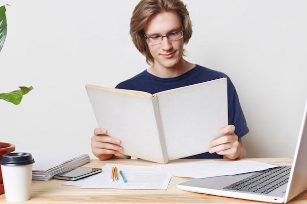 Studente maschio elegante e laborioso che indossa occhiali, ha uno sguardo attento nel libro, legge la letteratura scientifica prima di scrivere l'articolo, essendo coinvolto nello studio e nel lavoro. concetto di educazione