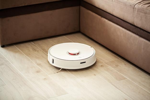 Smart house, robot aspirapolvere gira sul pavimento di legno in un salotto