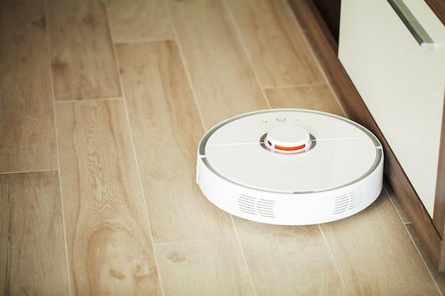 Smart house, robot aspirapolvere gira sul pavimento di legno in un salotto,
