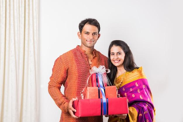 Coppia indiana intelligente in piedi con scatole regalo durante il festival di diwali o la cerimonia di matrimonio