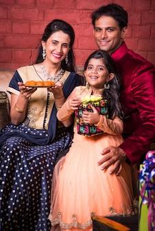 Intelligente famiglia indiana di quattro persone in abbigliamento etnico che tiene i regali diwali mentre è seduto sul divano, al coperto