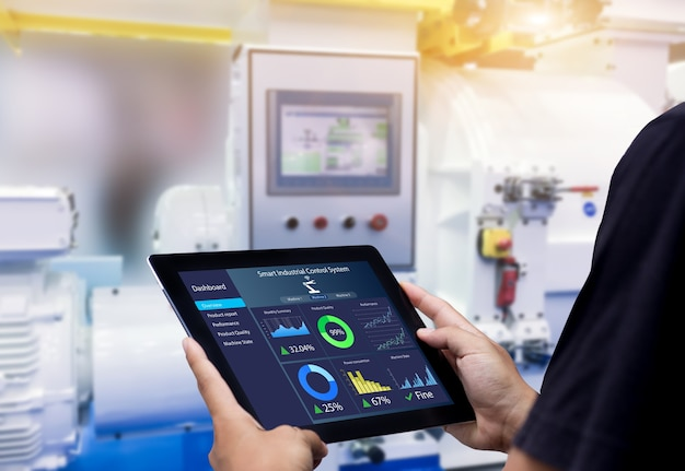 Concetto di controllo industriale intelligente. mani che tengono tablet sulla macchina di automazione sfocata come sfondo