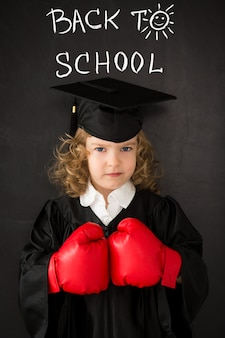 Ragazzo intelligente in classe. bambino felice contro la lavagna. di nuovo a scuola. la conoscenza è il concetto di potere