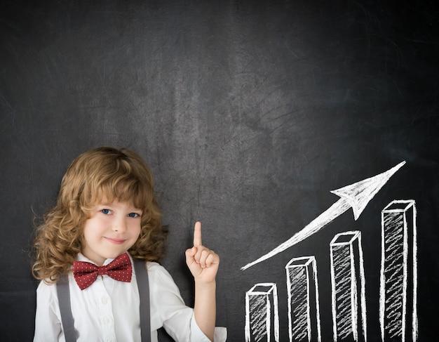 Ragazzo intelligente in classe. bambino felice contro la lavagna. disegno grafico a barre di crescita. concetto di affari
