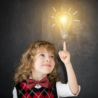 Ragazzo intelligente in classe. bambino felice contro la lavagna. lampadina di disegno. concetto di idea