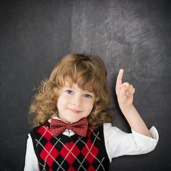 Ragazzo intelligente in classe. bambino felice contro la lavagna. concetto di educazione. copia spazio per il tuo testo