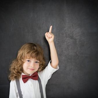 Ragazzo intelligente in classe. bambino felice contro la lavagna. concetto di educazione