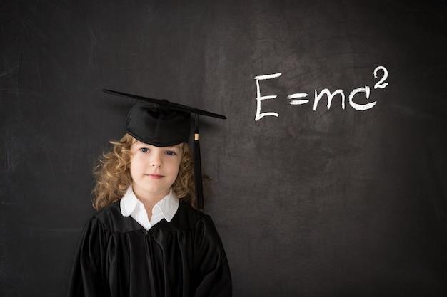 Ragazzo intelligente in classe. scolaro contro la lavagna. concetto di educazione