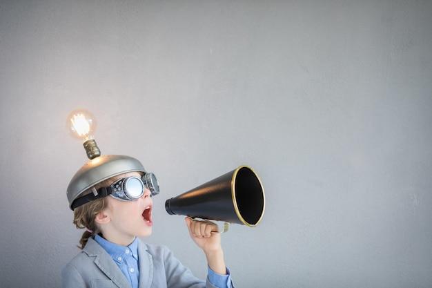 Ragazzo intelligente in classe. bambino con le cuffie da realtà virtuale giocattolo in classe. successo, idea e concetto creativo. di nuovo a scuola