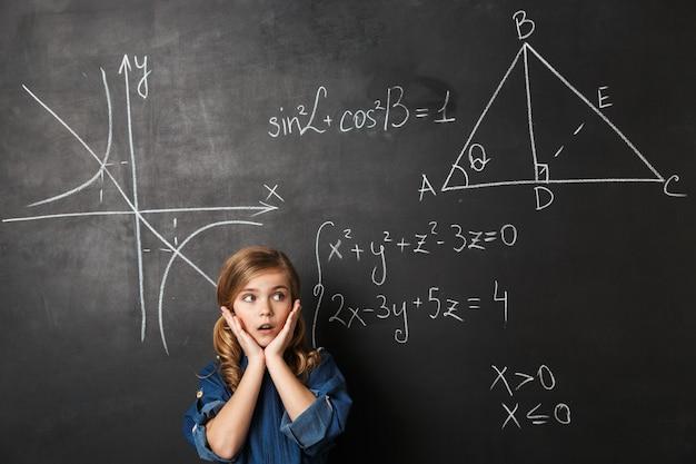 Piccola scolaretta intelligente in piedi alla lavagna con grafica matematica scritta su di essa
