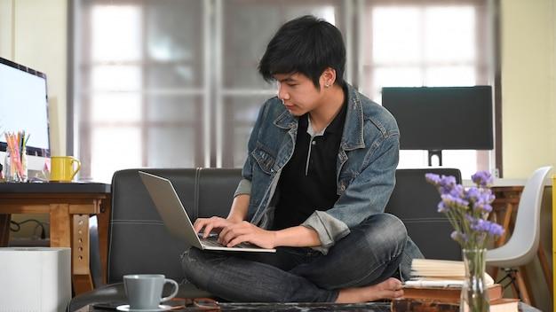 Un uomo intelligente sta scrivendo su un computer portatile che si mette in grembo mentre è seduto su un divano in pelle.