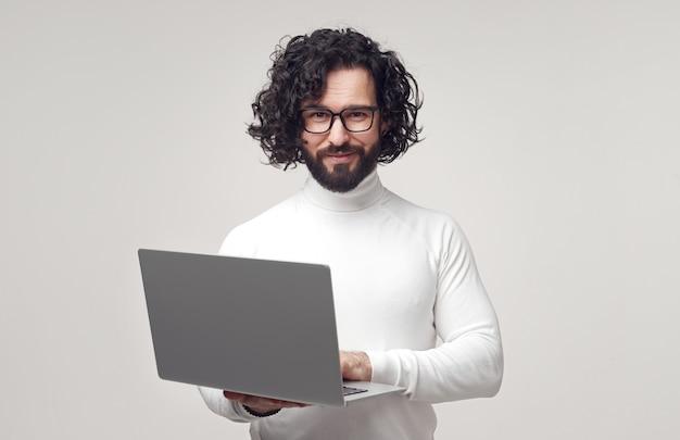 Uomo intelligente con laptop che guarda l'obbiettivo