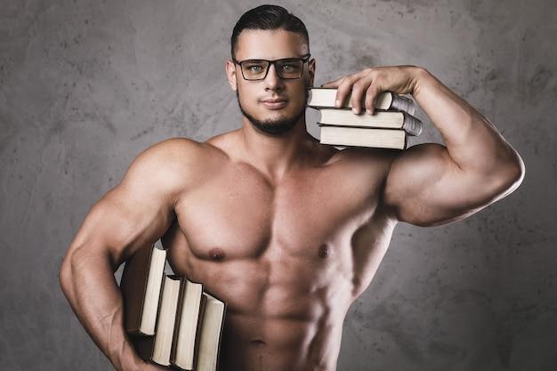 Uomo intelligente e muscoloso con un mucchio di libri