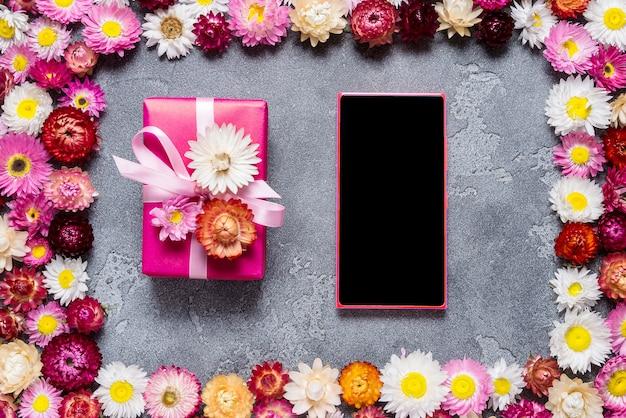 Smart phone e confezione regalo su sfondo floreale