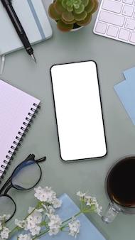 Smartphone circondato da notebook, tazza di caffè, bicchieri e piante succulente.