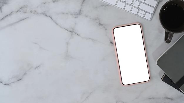Smart phone con schermo vuoto, tazza di caffè, tastiera e notebook su sfondo marmo.