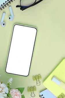 Smart phone con schermo vuoto, auricolari, fiori e notebook su sfondo verde.