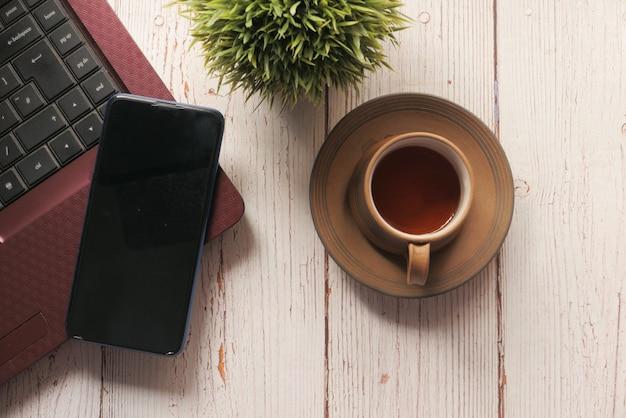 Smart phone con schermo vuoto, laptop sulla tavola di legno.