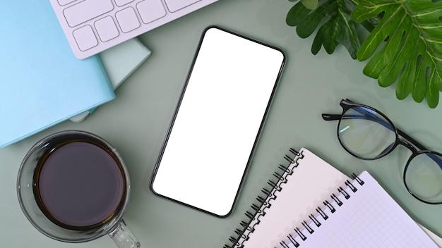 Smart phone con schermo vuoto sulla scrivania dell'ufficio.
