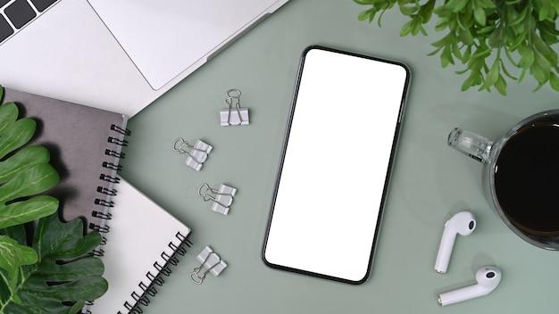 Smart phone con forniture per ufficio schermo vuoto sul tavolo grigio.