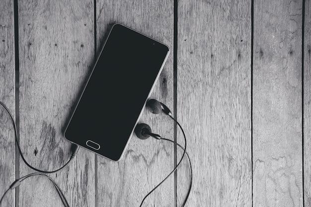 Smart phone con cavo di cuffie sul tavolo di legno