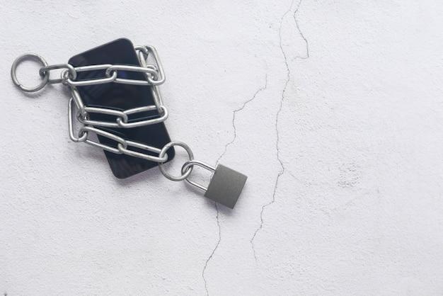 Smart phone con lucchetto e catena su sfondo bianco.