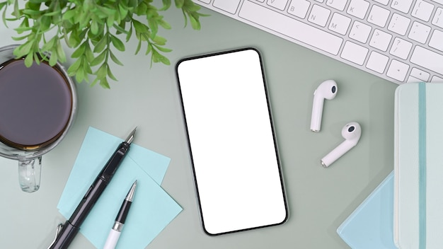 Smartphone con schermo bianco su un'area di lavoro disordinata.