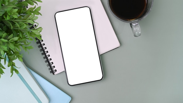 Smartphone con schermo bianco, taccuino, tazza di caffè e pianta di casa o scrivania.