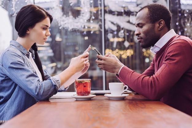 Coppie moderne piacevoli intelligenti che bevono bevande stando seduti e guardando i telefoni