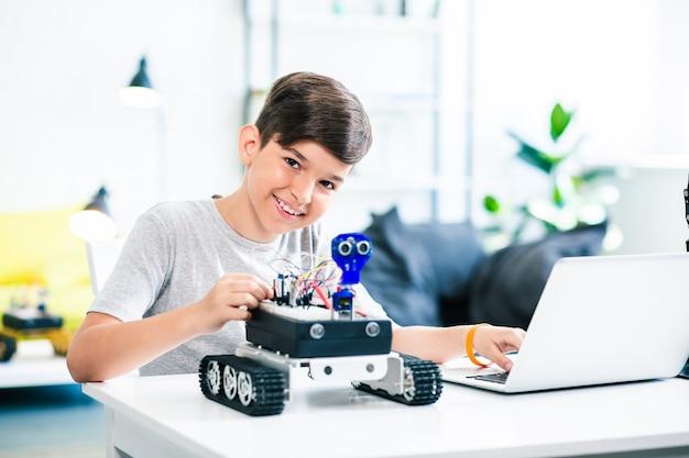 Ragazzo positivo intelligente che prova il robot mentre si prepara per le lezioni di ingegneria a casa