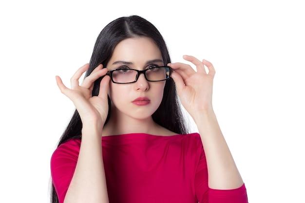 Giovane studentessa professionale intelligente in camicia rossa che tocca gli occhiali pensando a una nuova idea su sfondo bianco, idea di concetto di donna di conoscenza