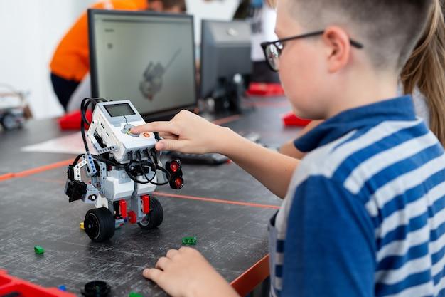 Scolaro intelligente seduto al tavolo e costruendo un dispositivo robotico in una lezione scolastica