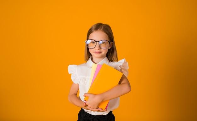 Studentessa intelligente con gli occhiali e una camicetta bianca tiene i libri di testo su uno sfondo giallo con una copia dello spazio