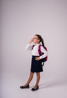 Una studentessa intelligente in uniforme con gli occhiali si erge su uno sfondo bianco con un posto per il testo