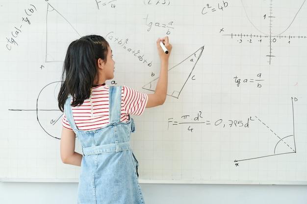 Studentessa intelligente che scrive sulla lavagna quando risolve il compito di geometria in classe, vista dal retro