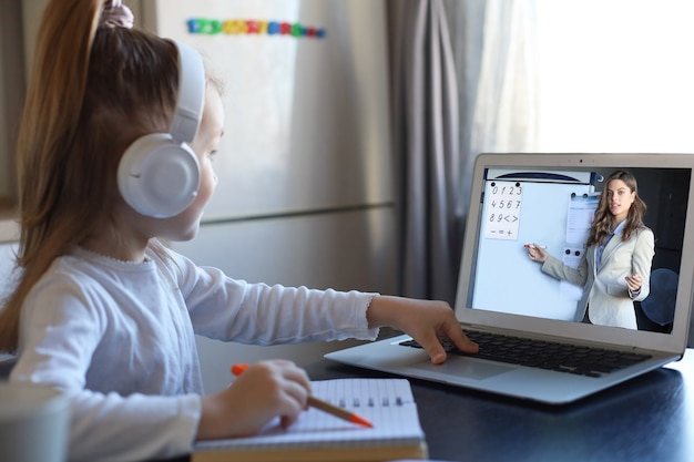 La piccola ragazza in età prescolare intelligente in cuffie guarda la lezione online e comunica con l'insegnante a casa, il bambino piccolo in auricolari studia su internet utilizzando la connessione wireless del laptop.