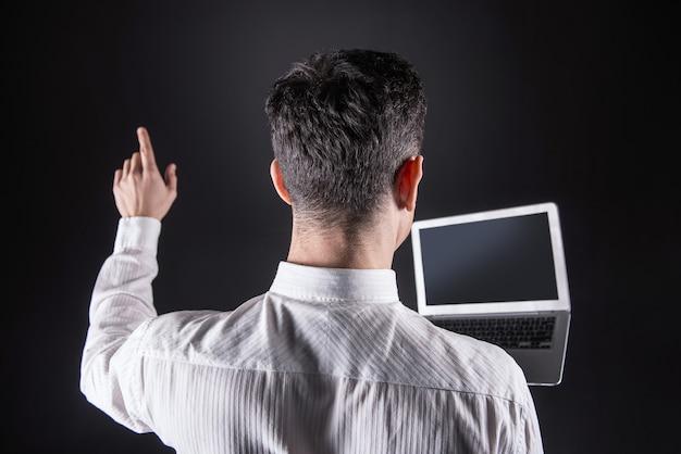 Tecnologia intelligente. uomo bello bello intelligente che tiene un computer portatile e ci lavora mentre utilizza la tecnologia digitale