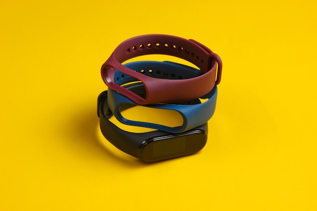Orologio smart con bracciali intercambiabili su sfondo giallo. tracker di fitness. gadget moderni