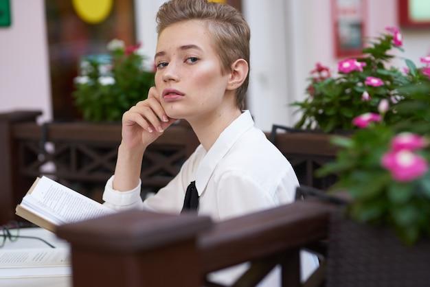 Donna intelligente con un libro si siede a un tavolo in un caffè e trucco primaverile di fiori rosa