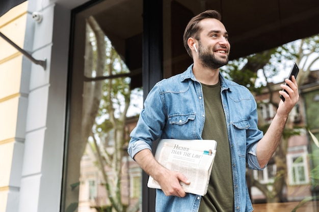 Giovane intelligente che indossa auricolari utilizzando lo smartphone mentre si cammina per la strada della città con giornali e laptop in mano