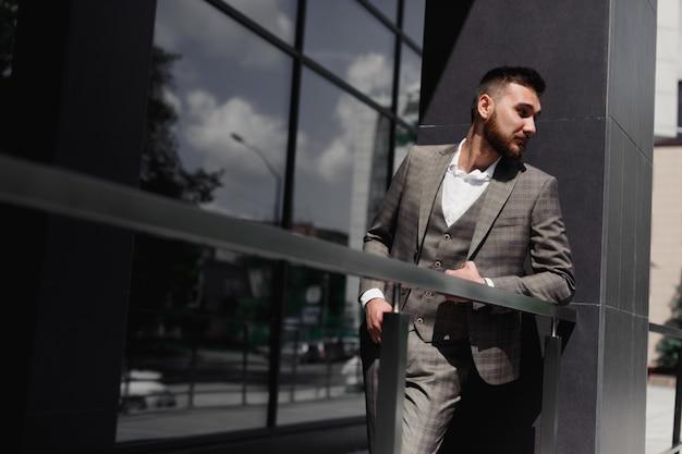 Uomo d'affari elegantemente vestito, uomo d'affari moderno. fiducioso giovane uomo in tuta intera in piedi all'aperto con la costruzione in background