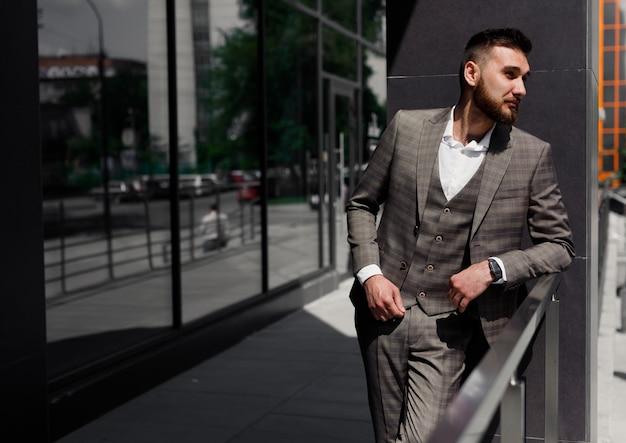 Uomo d'affari elegantemente vestito che posa nell'edificio