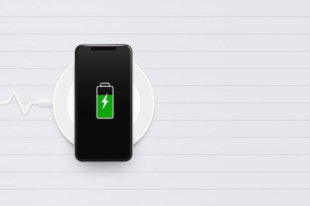 Smartphone che carica l'energia sul nuovo dispositivo caricabatteria su fondo di legno bianco con lo spazio della copia