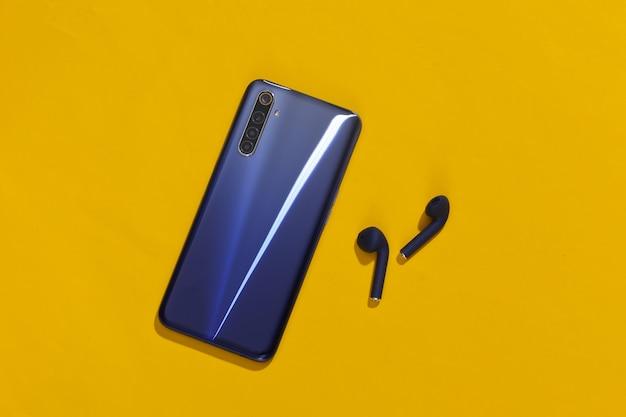 Smartphone e auricolari bluetooth senza fili classici di colore blu classico su sfondo giallo brillante.